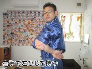 巻き肩反対の手で肘を持つ