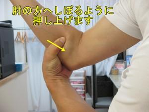 左手は押えたまま力を緩めずに肘の方へ上げています。