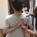 肩甲骨はがしで背中で指を組み自分の肩甲骨を指す