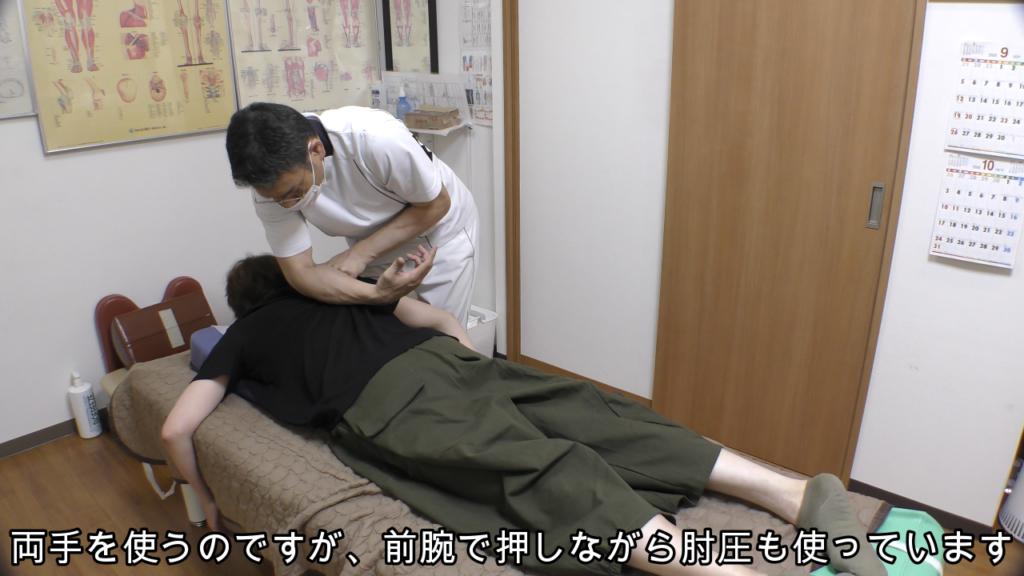 前腕で肩甲骨に指を押し込みながら肘で背中も押す